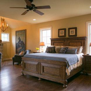 Immagine di una camera matrimoniale country di medie dimensioni con pareti gialle, pavimento in legno massello medio, camino lineare Ribbon e cornice del camino in pietra