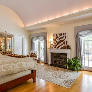 Photo of a large traditional master bedroom in New York with beige walls, medium hardwood floors, a standard fireplace, a metal fireplace surround and brown floor.