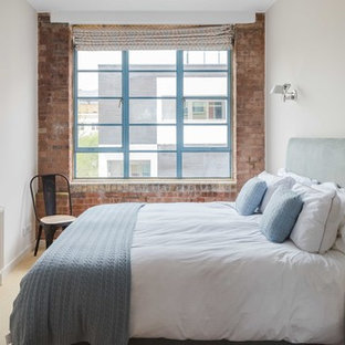 Photo of an industrial bedroom in London with white walls, carpet and beige floors.
