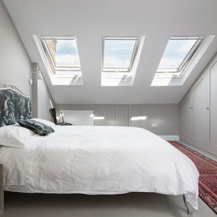 Medium sized contemporary guest bedroom in London with grey walls, carpet and grey floors.