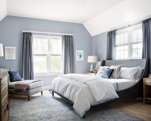 large transitional guest bedroom photo in new york with blue walls and medium tone hardwood floors - Calming Bedroom Color Schemes
