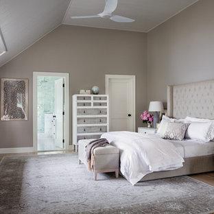 Ejemplo de dormitorio principal, clásico renovado, sin chimenea, con paredes marrones y suelo de madera clara