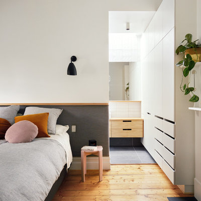 Bedroom - small contemporary master brown floor and medium tone wood floor bedroom idea in Melbourne with white walls and a standard fireplace