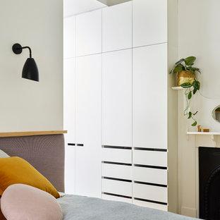 Foto de dormitorio principal, moderno, pequeño, con paredes blancas, suelo de madera clara, chimenea tradicional, marco de chimenea de madera y suelo marrón