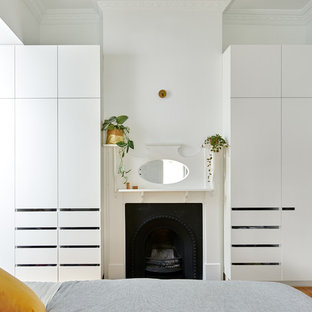 Photo of a small contemporary master bedroom in Melbourne with white walls, a standard fireplace, a wood fireplace surround, brown floor and medium hardwood floors.