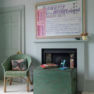 Country bedroom in Other with green walls, painted wood floors and a standard fireplace.
