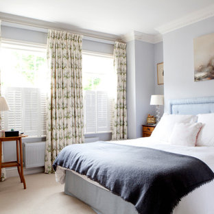 Inspiration for a medium sized traditional master bedroom in London with carpet, blue walls and beige floors.