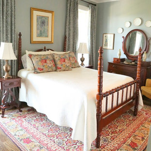 This is an example of a traditional bedroom in Nashville with grey walls and medium hardwood floors.