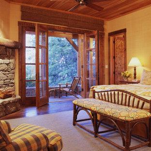 Ejemplo de dormitorio rural con chimenea de esquina y marco de chimenea de piedra