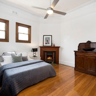 Modern guest bedroom in Sydney with white walls, medium hardwood floors, a corner fireplace and a wood fireplace surround.