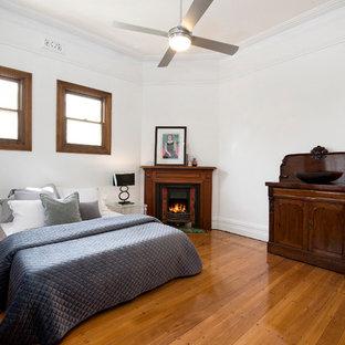 Modelo de habitación de invitados minimalista con paredes blancas, suelo de madera en tonos medios, chimenea de esquina y marco de chimenea de madera