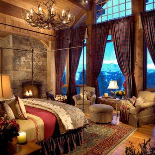 Idéer för att renovera ett rustikt sovrum, med mellanmörkt trägolv, en spiselkrans i sten och en standard öppen spis