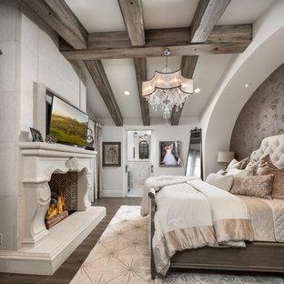Ejemplo de dormitorio principal, moderno, extra grande, con paredes beige, suelo de madera oscura, chimenea de doble cara, marco de chimenea de piedra y suelo marrón