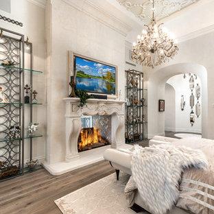 Foto di un'ampia camera matrimoniale shabby-chic style con pareti beige, parquet scuro, camino bifacciale, cornice del camino in pietra e pavimento marrone