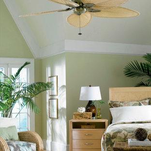 Ejemplo de dormitorio principal, exótico, de tamaño medio, sin chimenea, con paredes verdes y suelo de madera en tonos medios