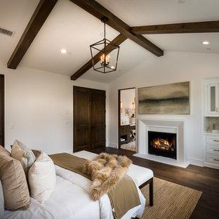 Ejemplo de dormitorio principal, mediterráneo, con paredes blancas, suelo de madera oscura, chimenea tradicional y marco de chimenea de yeso