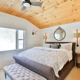 Example of a cottage guest medium tone wood floor and beige floor bedroom design in New York with white walls