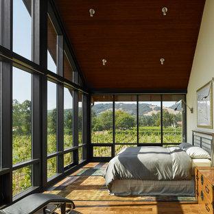 Foto de dormitorio campestre con paredes beige, suelo de madera en tonos medios y suelo marrón