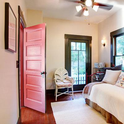 Cottage guest medium tone wood floor bedroom photo in Los Angeles with beige walls