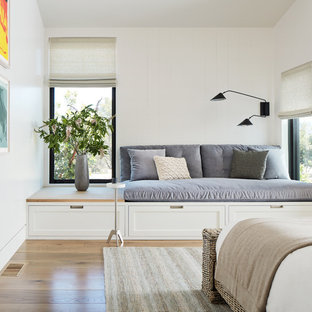 Country master medium tone wood floor bedroom photo in San Francisco with white walls