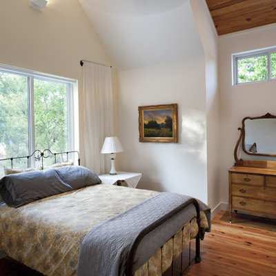 Example of a farmhouse medium tone wood floor bedroom design in Austin with white walls