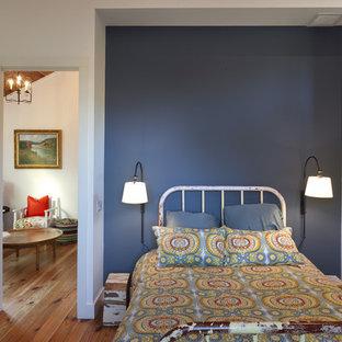 Imagen de habitación de invitados campestre, sin chimenea, con paredes azules y suelo de madera en tonos medios