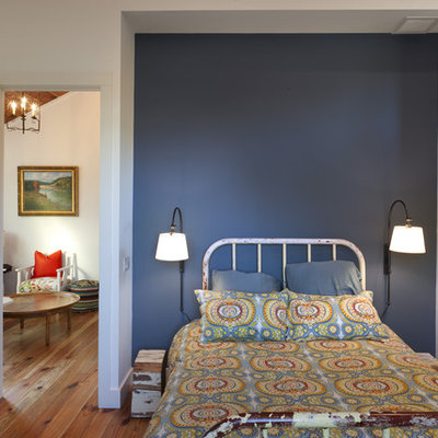 Country guest medium tone wood floor bedroom photo in Austin with blue walls and no fireplace