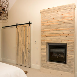 Mid-sized country master bedroom in Other with beige walls, carpet, a standard fireplace and a wood fireplace surround.