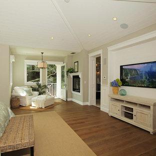 Ejemplo de dormitorio principal, campestre, grande, con paredes beige, suelo de madera en tonos medios, chimenea de doble cara y marco de chimenea de madera