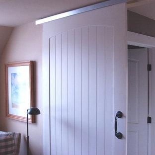 Ejemplo de dormitorio principal, de estilo de casa de campo, grande, sin chimenea, con paredes beige, suelo de baldosas de cerámica y suelo blanco