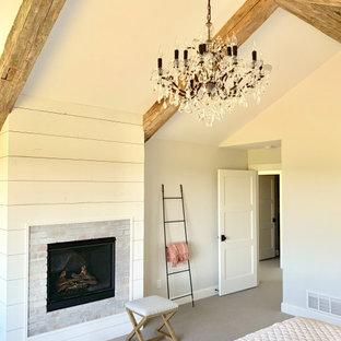 Immagine di una grande camera matrimoniale country con pareti grigie, moquette, camino classico, cornice del camino in mattoni e pavimento grigio