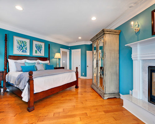 coastal medium tone wood floor bedroom photo in with blue walls and a standard fireplace