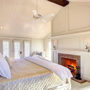 Ejemplo de dormitorio principal, clásico, grande, con paredes blancas, suelo de madera en tonos medios, chimenea tradicional y marco de chimenea de ladrillo