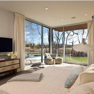 Immagine di una camera matrimoniale minimalista con pareti beige e moquette