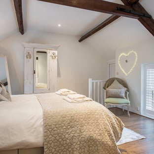 Photo of a medium sized farmhouse bedroom in Other with white walls, medium hardwood flooring and brown floors.