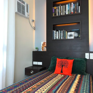 Example of a small eclectic guest medium tone wood floor and yellow floor bedroom design in Other with beige walls and no fireplace