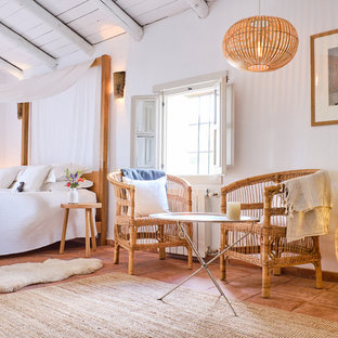 Design ideas for a country bedroom in London with white walls, terracotta flooring and brown floors.
