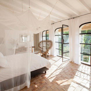 На фото: хозяйская спальня в средиземноморском стиле с белыми стенами и полом из терракотовой плитки с