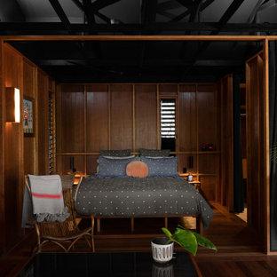 Exemple d'une chambre exotique en bois avec un mur marron, un sol en bois foncé et un sol marron.