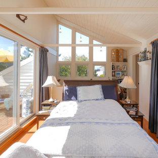 Ejemplo de dormitorio tipo loft, de tamaño medio, con paredes blancas, suelo de madera en tonos medios, estufa de leña y suelo marrón