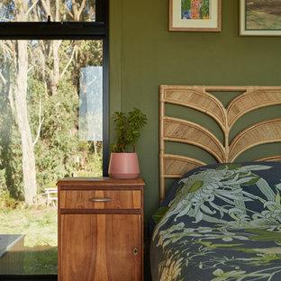 Bild på ett funkis sovrum, med gröna väggar, mellanmörkt trägolv och brunt golv
