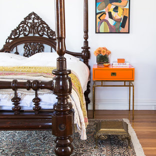 Inspiration for an expansive eclectic master bedroom in Melbourne with white walls, medium hardwood floors and brown floor.
