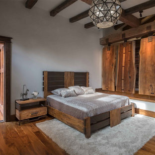 Inspiration for a large rustic master medium tone wood floor bedroom remodel in Phoenix with white walls