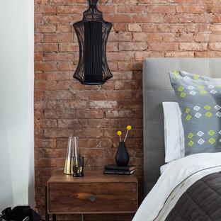 Diseño de dormitorio tipo loft, industrial, pequeño, con suelo de madera oscura, chimenea de doble cara, marco de chimenea de yeso y suelo marrón
