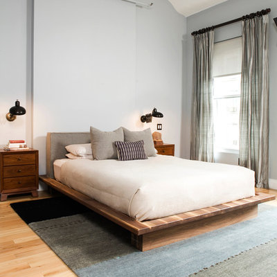 Example of a large eclectic master light wood floor bedroom design in New York with gray walls and no fireplace
