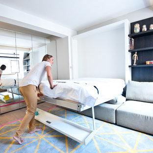 Foto de dormitorio principal, minimalista, pequeño, con paredes blancas, suelo de madera oscura, chimenea tradicional y marco de chimenea de yeso