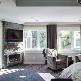 Imagen de dormitorio principal, actual, grande, con paredes grises, moqueta, chimenea de esquina, marco de chimenea de ladrillo y suelo gris