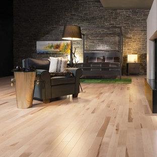 Imagen de dormitorio tipo loft, urbano, grande, con paredes grises, suelo de madera clara, chimenea de doble cara y marco de chimenea de hormigón