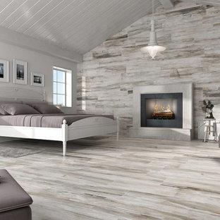 Modelo de dormitorio principal, actual, grande, con paredes grises, suelo de baldosas de porcelana, chimenea tradicional y marco de chimenea de hormigón