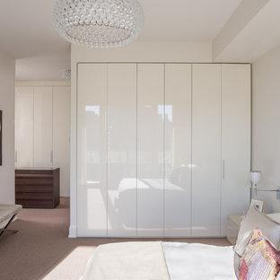 Idee per una camera matrimoniale design di medie dimensioni con pareti bianche e moquette